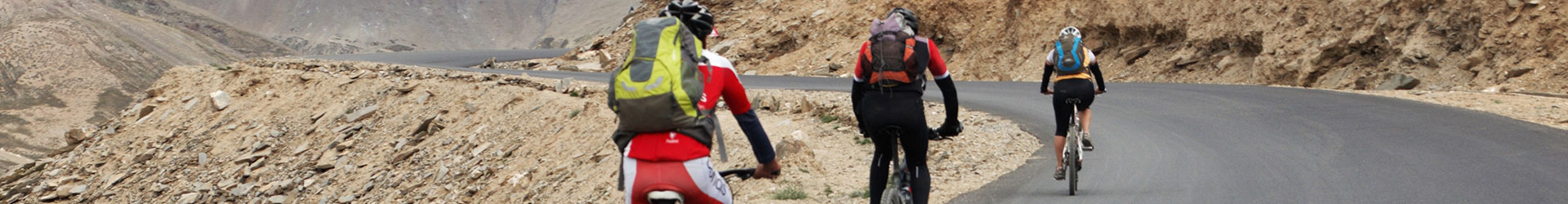 3 loaded bike riders cycling on-road tarmac