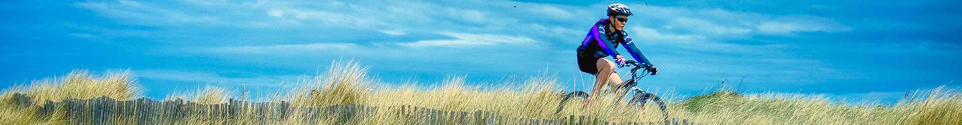 male bike rider cycling grass, blue sky background