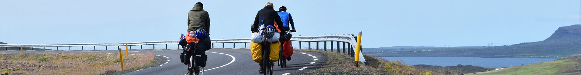 tour cycling, three riders with loaded bikes on highway